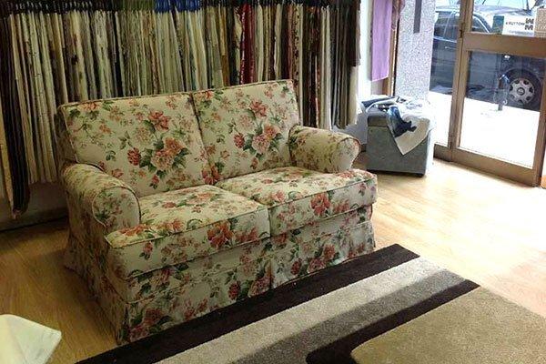 un divano a due posti di color giallo a fiori rossi e verdi e dietro le stoffe esposte