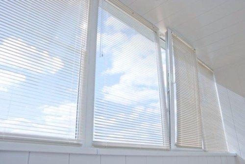 Finestre basculanti di PVC bianco coperte da veneziane bianche
