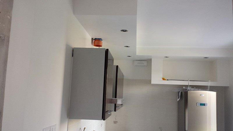 interno di una stanza appena imbiancata con vista di un frigo e un mobiletto a muro