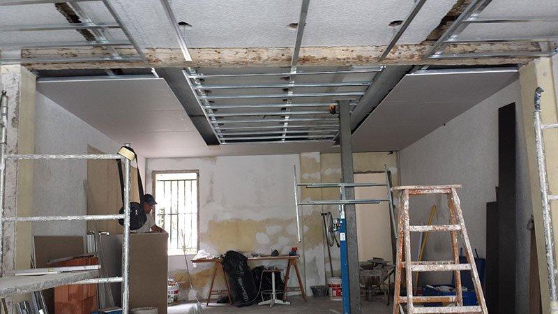 delle scale, un operaio e delle piccole impalcature in un appartamento in fase di ristrutturazione