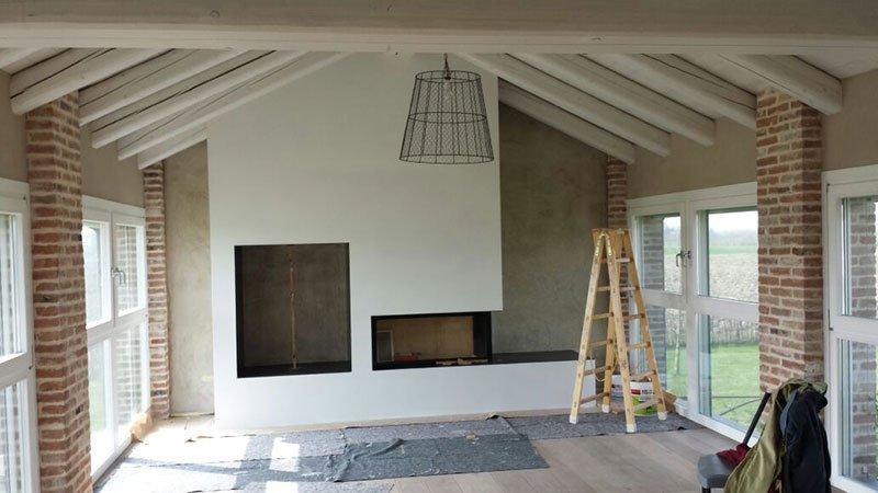 una stanza imbiancata con un lampadario, una scala di legno e vista delle finestre