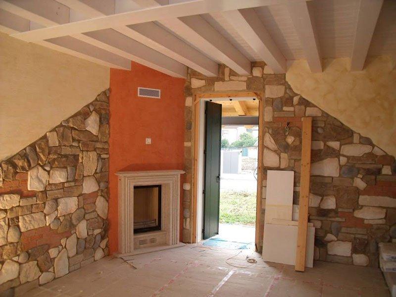 interno di una casa con muri in pietra, rosa e le finiture bianche di un camino