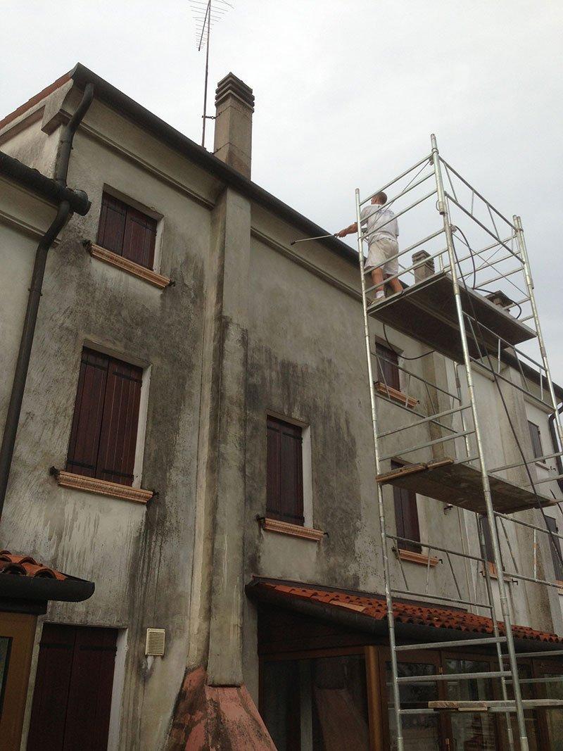 una casa con facciata sporca e un imbianchino su un impalcatura