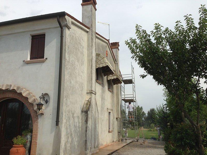 una casa con la facciata sporca e un impalcatura viste di lato