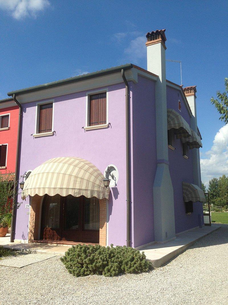 una casa con facciata viola chiara e una tenda da esterno