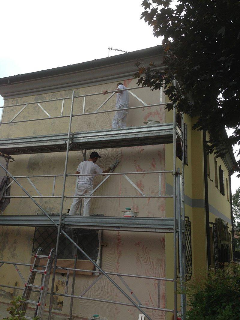 due operai su un impalcatura al lavoro su una facciata