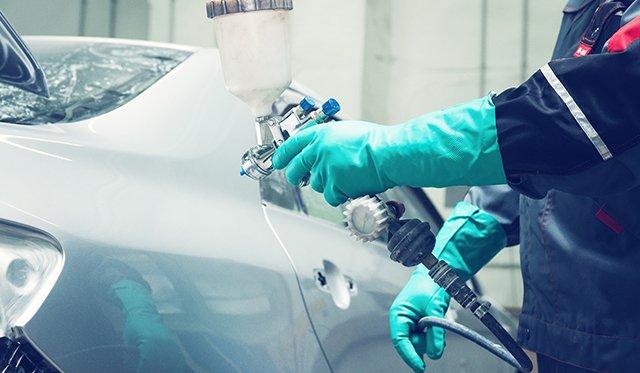 operaio vernicia un'auto con la pistola a spruzzo