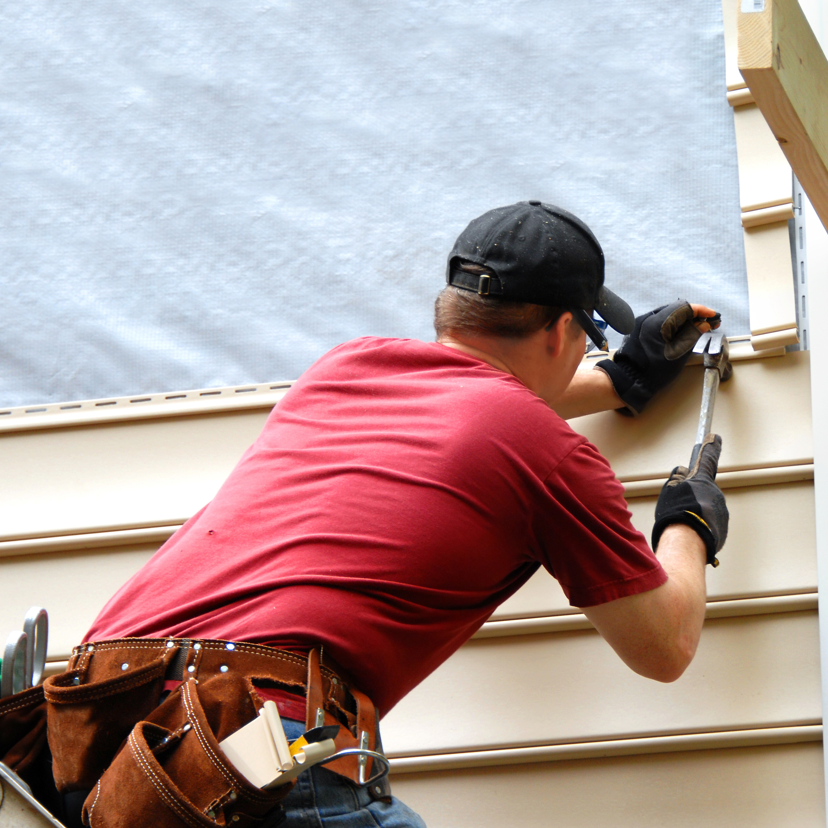 A worker adding siding to a house