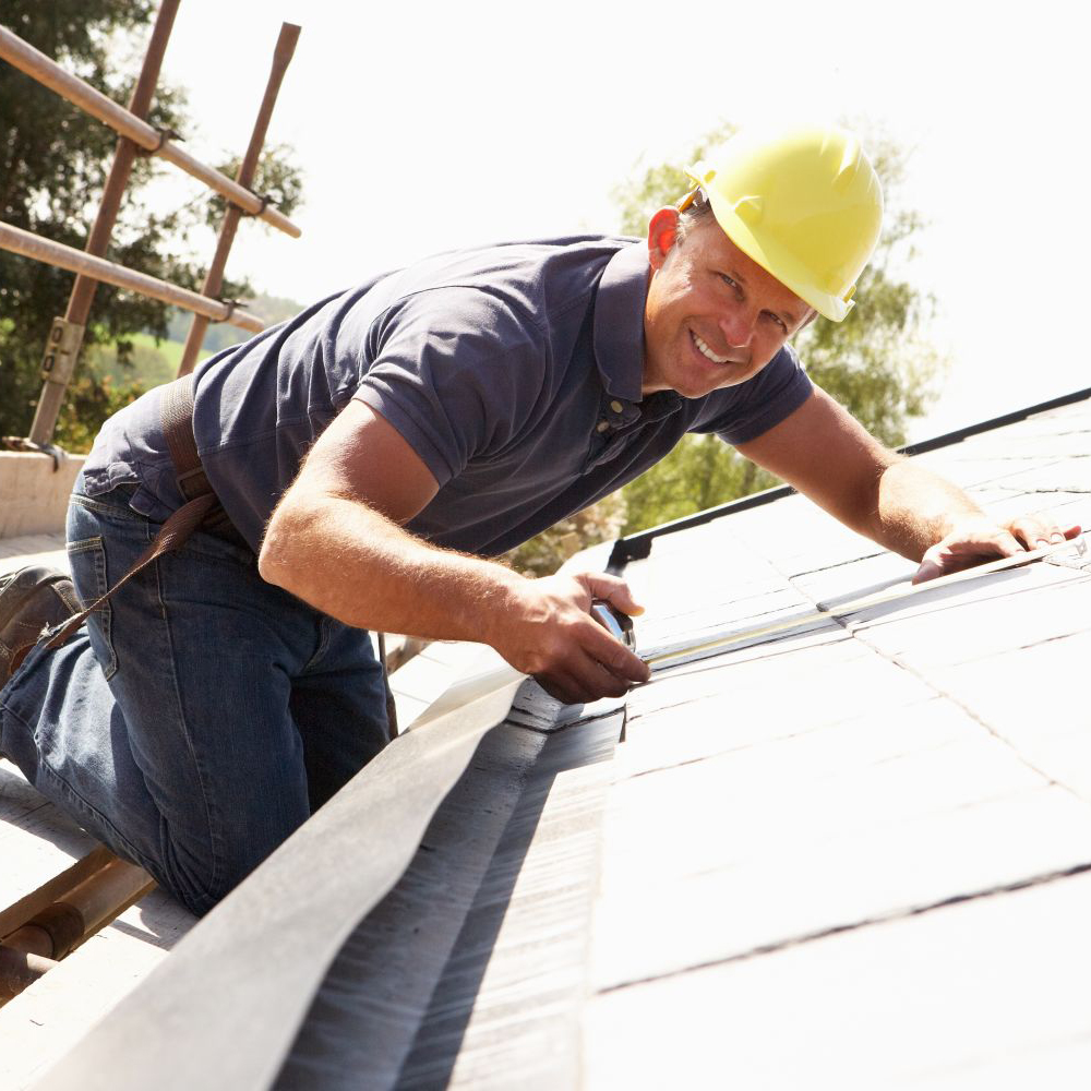 A worker measuring the roof of a house