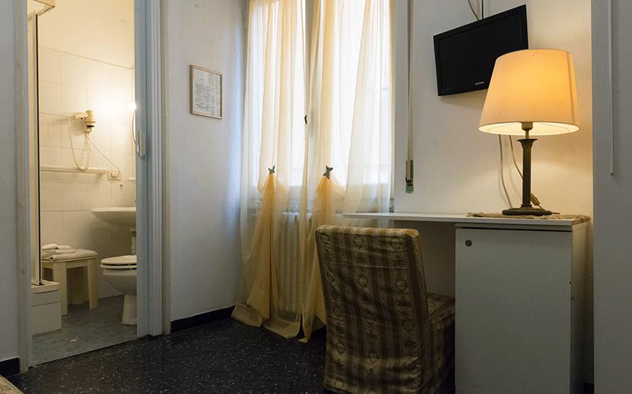 Dettaglio di camera con scrivania e porta-finestra