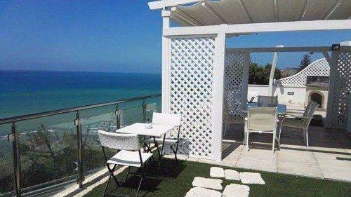 Pergola bianca e mobili bianchi, terrazza di fronte al mare