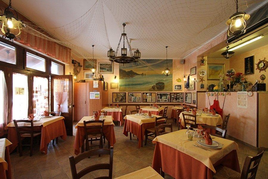 Un altro angolo dell'interno del ristorante con la porta di ingresso