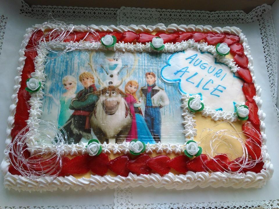 una torta da compleanno  di panna e fragole con scritto Auguri Alice e l'immagine di alcuni personaggi tratti da dei cartoni animati