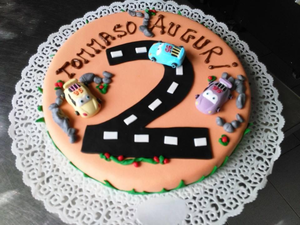 una torta a forma di hamburger di color arancione con 2 scritto Tommaso Auguri 2 e alcune macchinine sopra