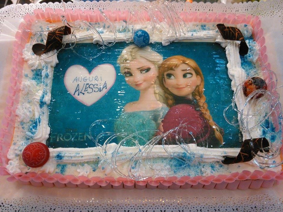 torta a forma rettangolare con panna,decorazioni, scriita Auguri Alessia e al centro il disegno di Frozen, personaggio tratto da un cartone animato