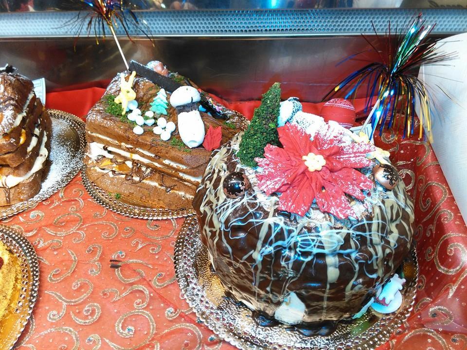 esposizione di torte color marrone decorate con disegni di una rosa,un albero e nell'altra un fungo