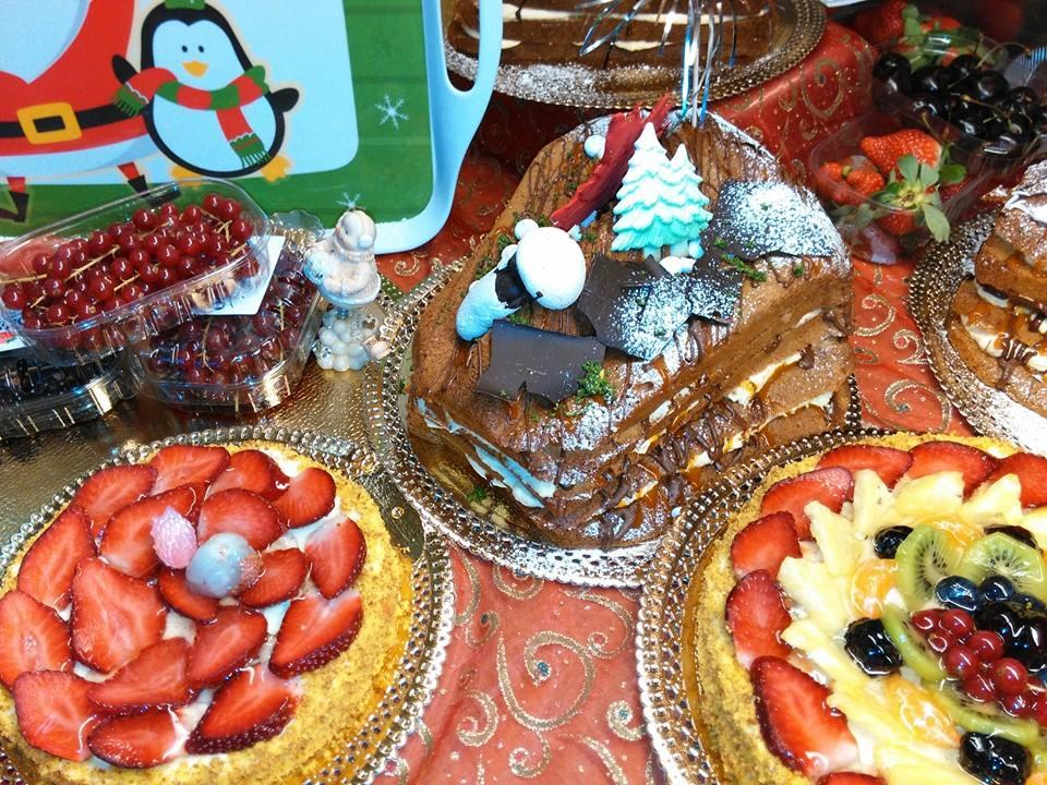 esposizione di torte di diversi tipi, alla fragola, alla crema pasticcera con kiwi e frutti di bosco, una vaschetta di  uva e altre torte