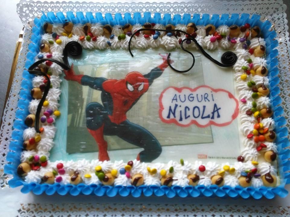 torta blu  e bianca di panna con Smarties, scritta Auguri Nicola e immagine dell'Uomo Ragno al centro