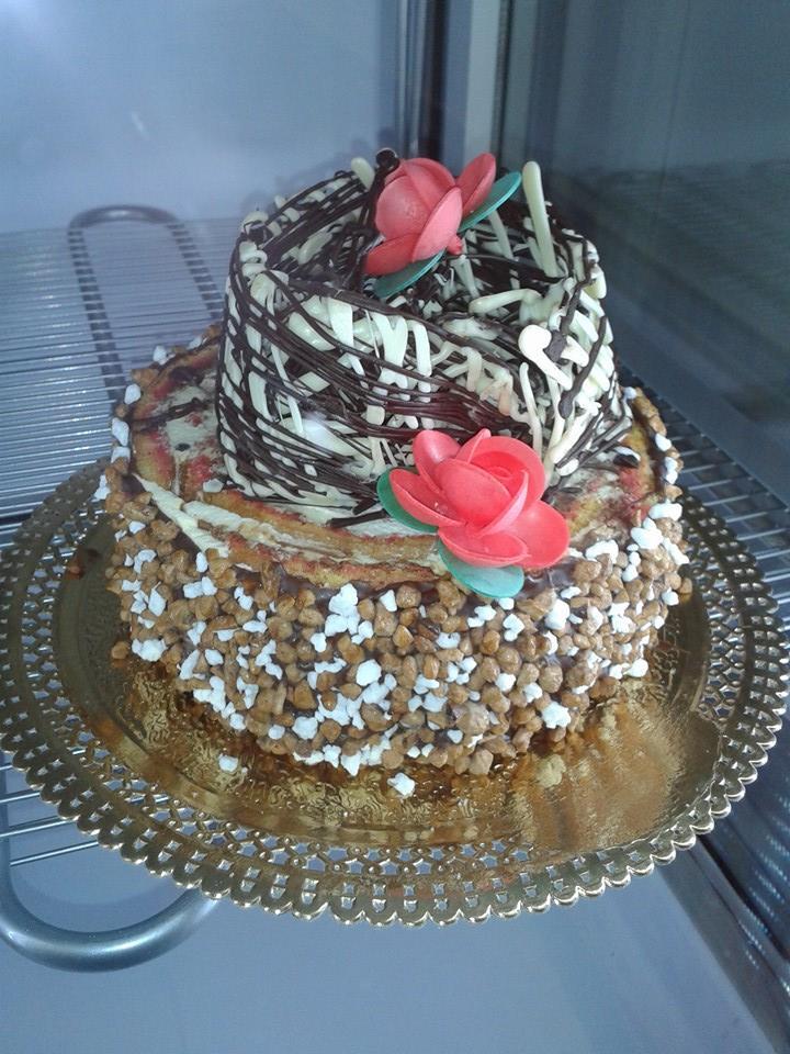 torta a 2 piani con praline glassa di panna e cioccolato con due fiori rosa sopra