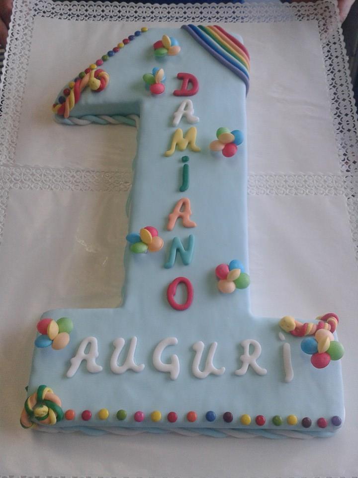 torta a forma di numero 1 con glassa color azzurro e scritta colorata Damiano Auguri