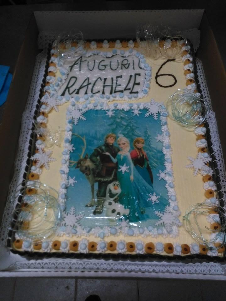 torta con decorazioni di panna sulle estremita' con scritta Auguri Rachele e al centro il disegno dei personaggi del cartone animato Frozen