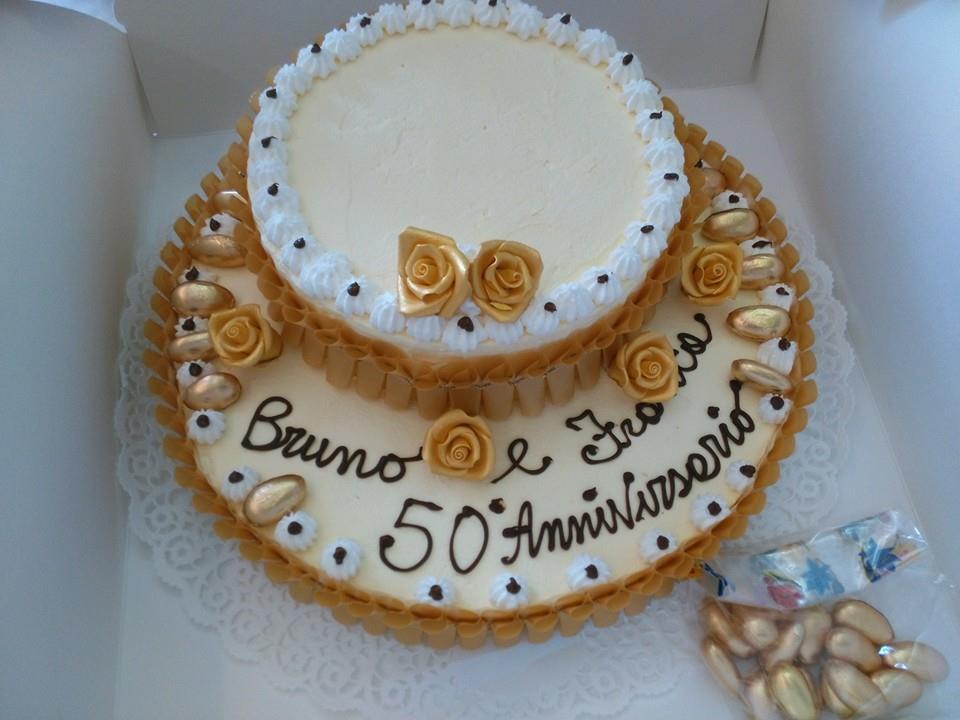 torta alla panna a 2 piani con scritto Bruno e Franca 50 Anniversario e delle rose fatte di glassa