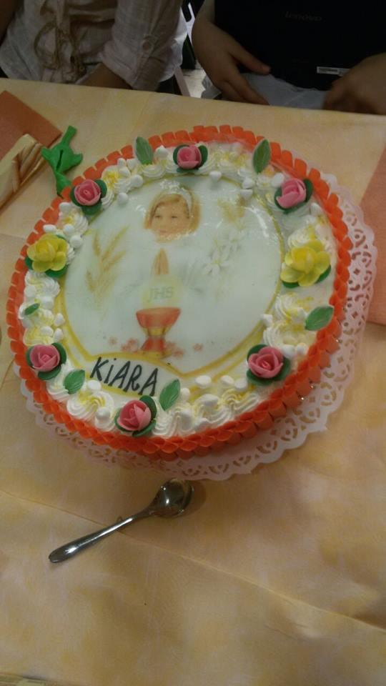 torta alla panna con fiori di glassa gialli e rosa e al centro la foto di una bambina bionda con un cerchietto per capelli di color bianco in testa