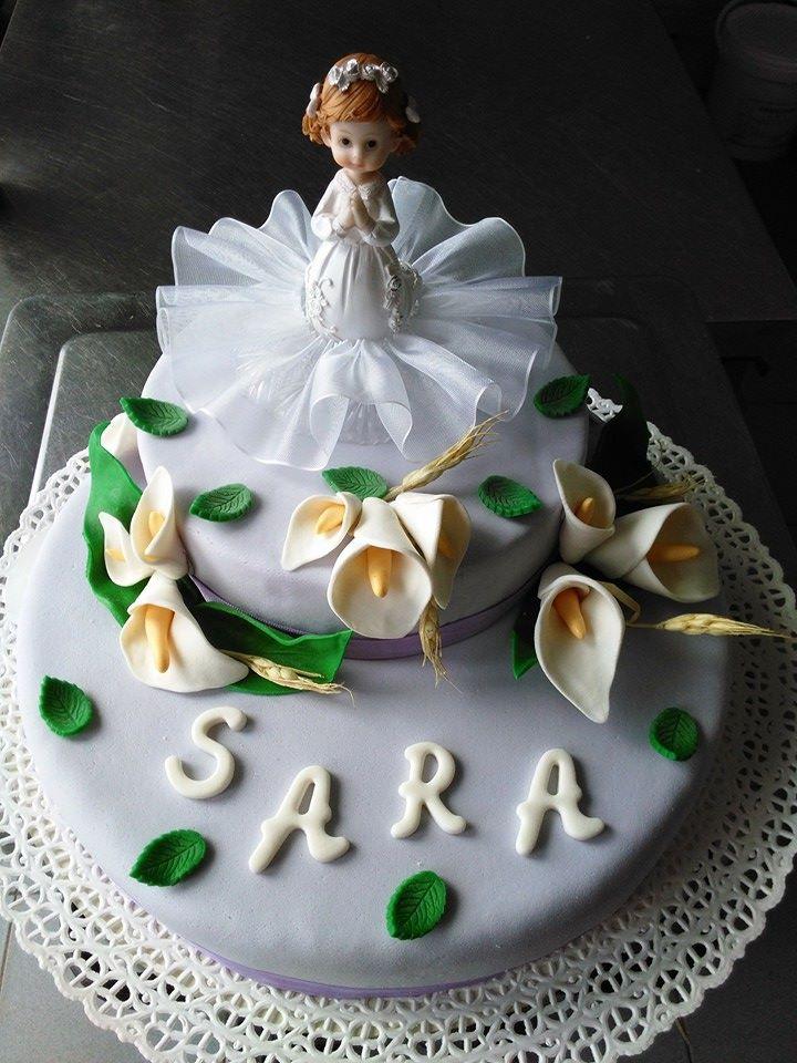 torta ricoperta di glassa bianca con fiori bianchi e sopra il pupazzo di una bambina vestita da sposa