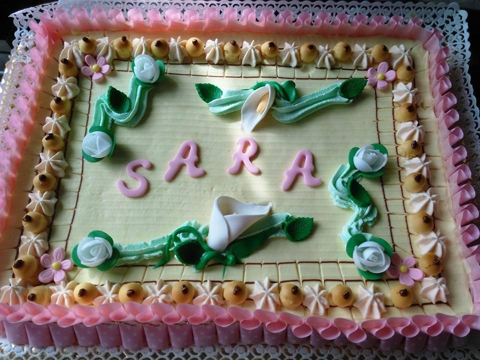 torta di panna e glassa di color rosa bianca e verde decorata con dei fiori bianchi e la scritta Sara