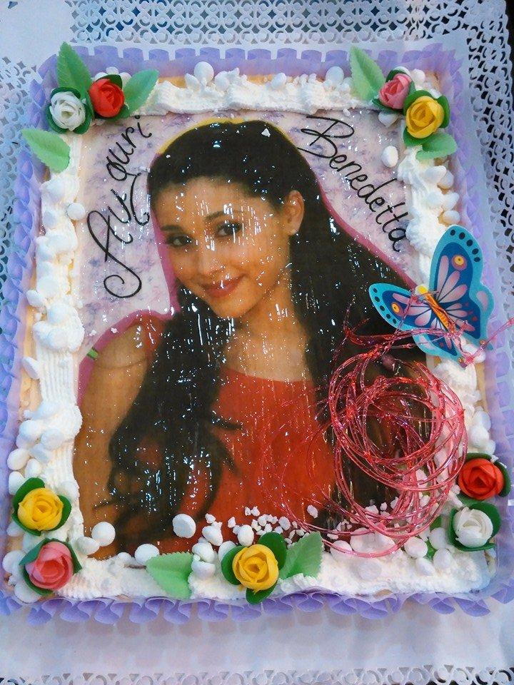 torta rettangolare alla panna con fiori di glassa rosa,gialli e bianchi, delle farfalle e foto di una ragazza con scritto Auguri Benedetta