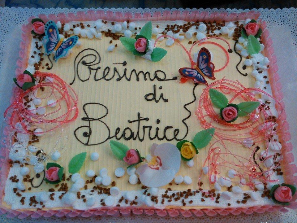 torta ricoperta di glassa con  farfalle blu, fiori rosa, panna, praline e scritta al centro Cresima di Beatrice