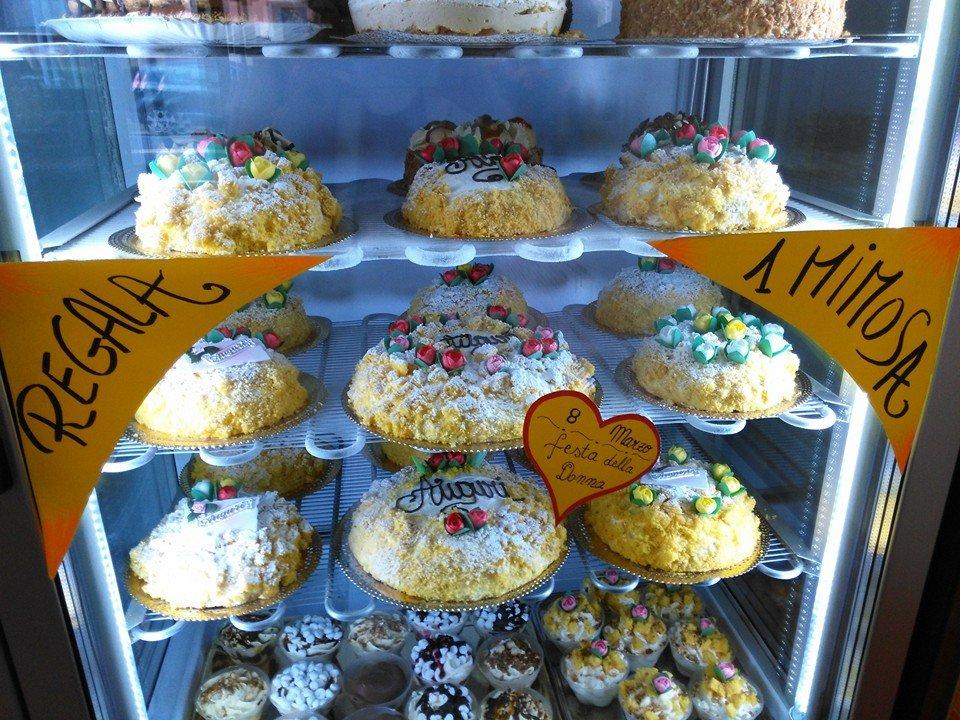 esposizione di torte per la Festa della Donna di color giallo con zucchero a velo, scritte di auguri, il tutto esposto nella vetrina