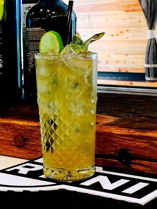 un bicchiere con un cocktail e delle fette di lime