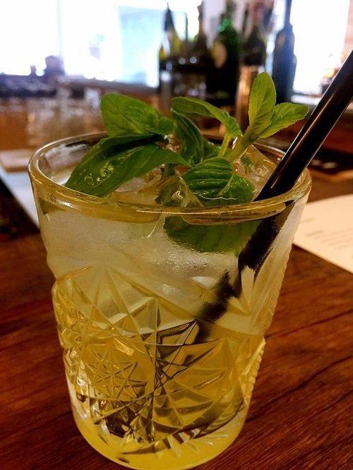 un bicchiere con un cocktail e delle foglie di menta