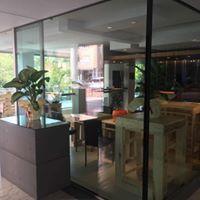 una vetrata e dietro vista dei tavoli con delle piante