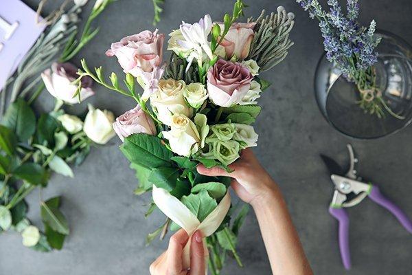 mani di donna preparano un bouquet di rose gialle e rosa