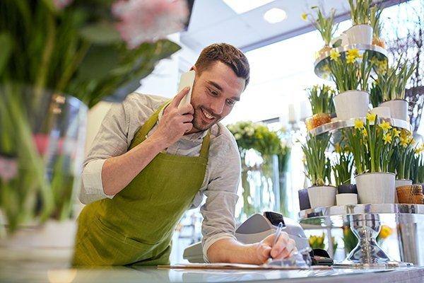 fiorista nel negozio prende appunti mentre e' al telefono