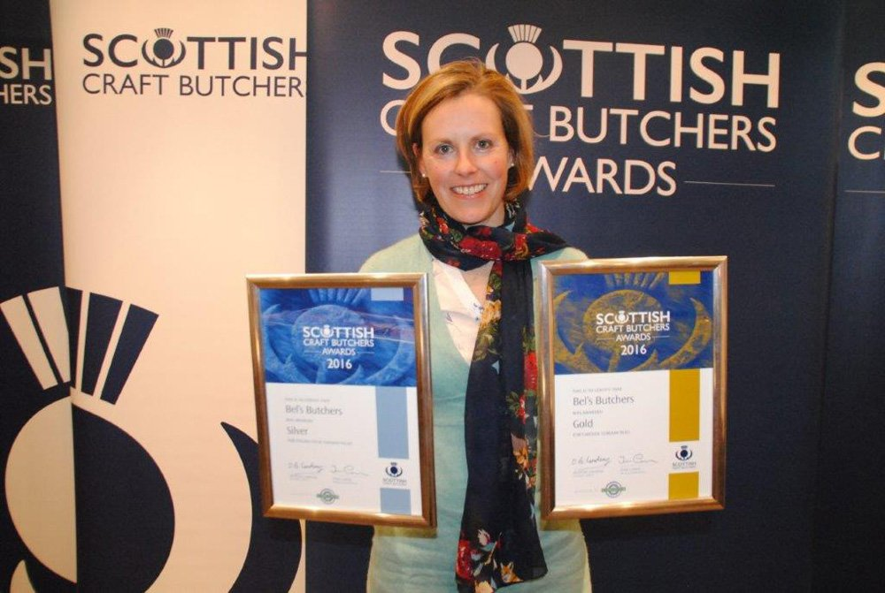 Women showing the awards won by Bel's butchers
