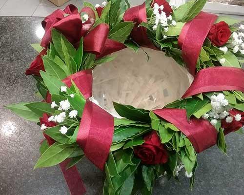 Paniere decorata con foglie di alloro . rose rosse, fiori silvstri bianche e nastro rossa