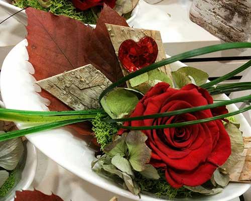 composizione con rosa rossa e foglie secche