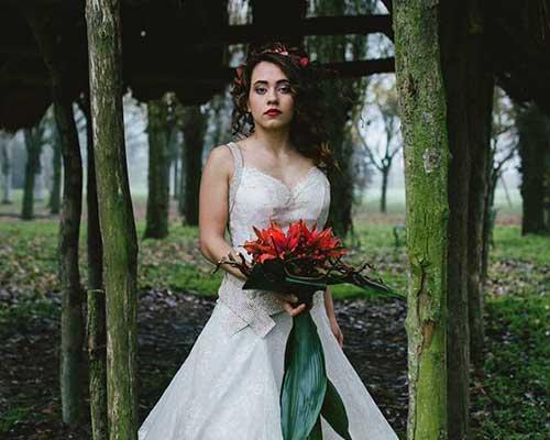 Sposa in foresta con bouquet di rose rosse