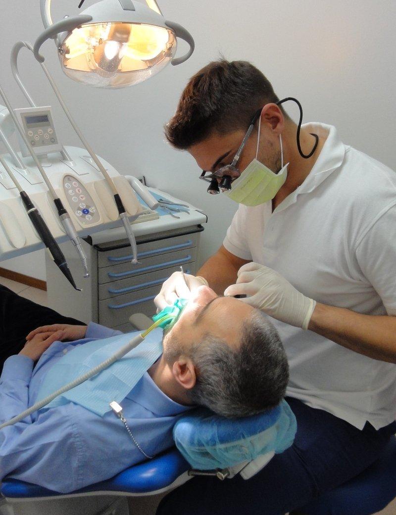 Dottor Alberto mainardi opera un paziente nel suo studio dentistico