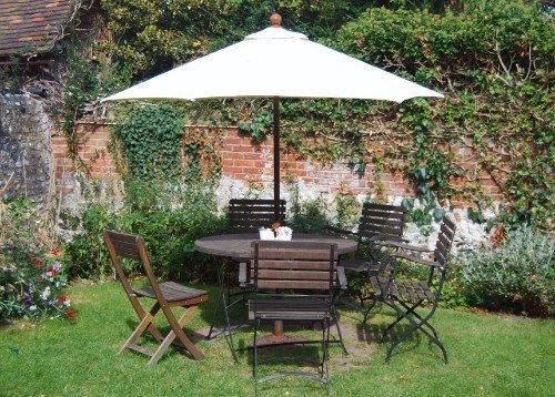 Un tavolo con delle sedie e un ombrellone in un giardino