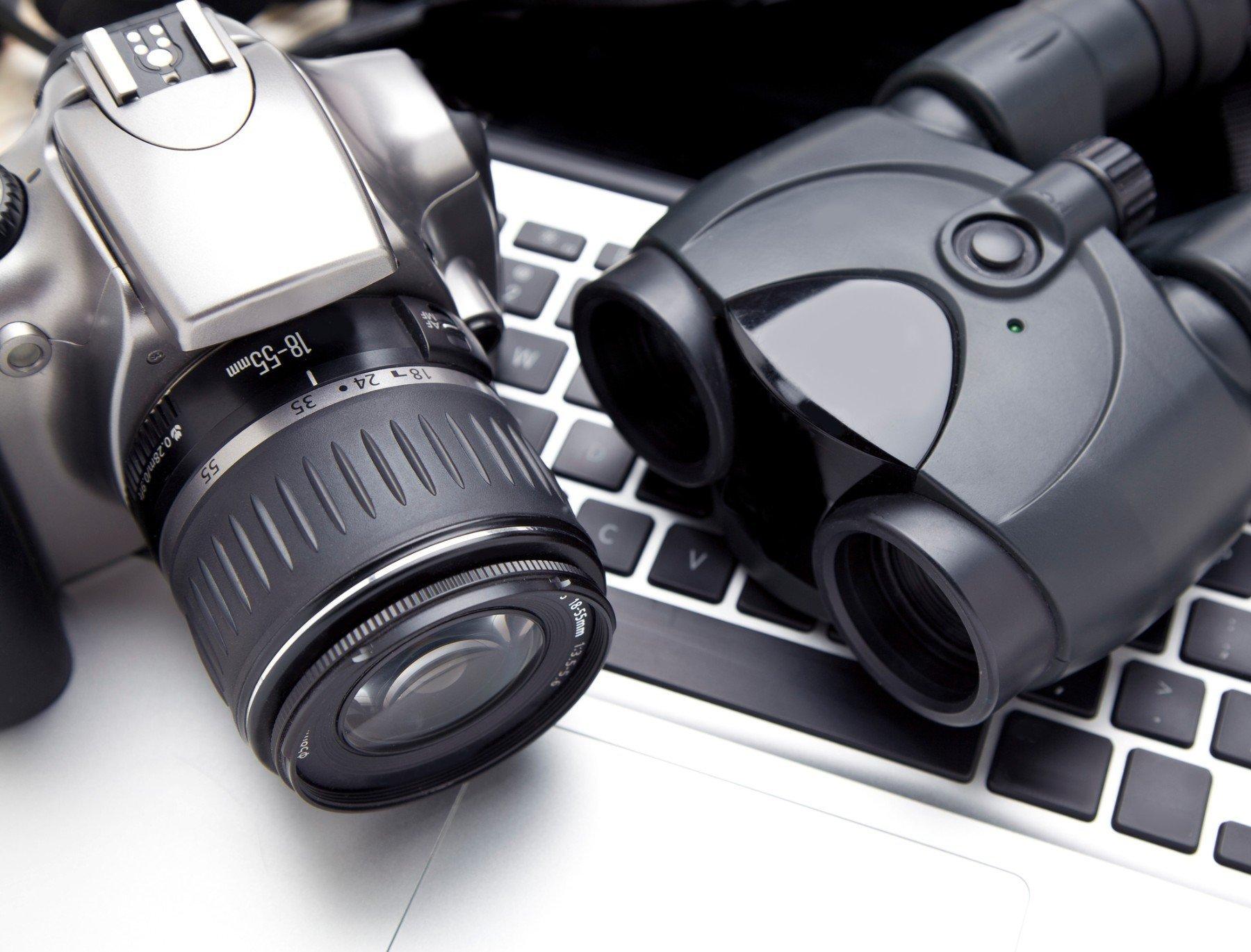 una macchina fotografica, un binocolo ed una tastiera di un computer