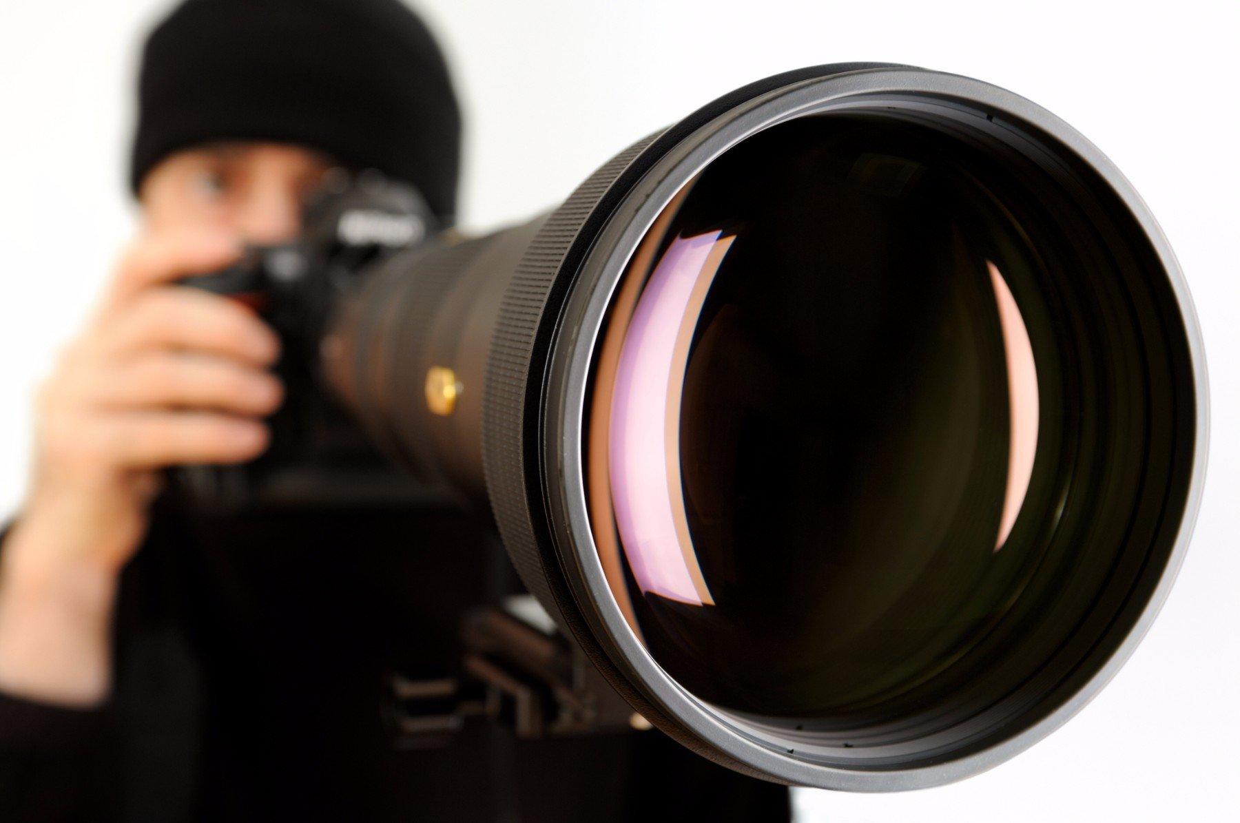 un primo piano di un fotografo con una macchina fotografica professionale