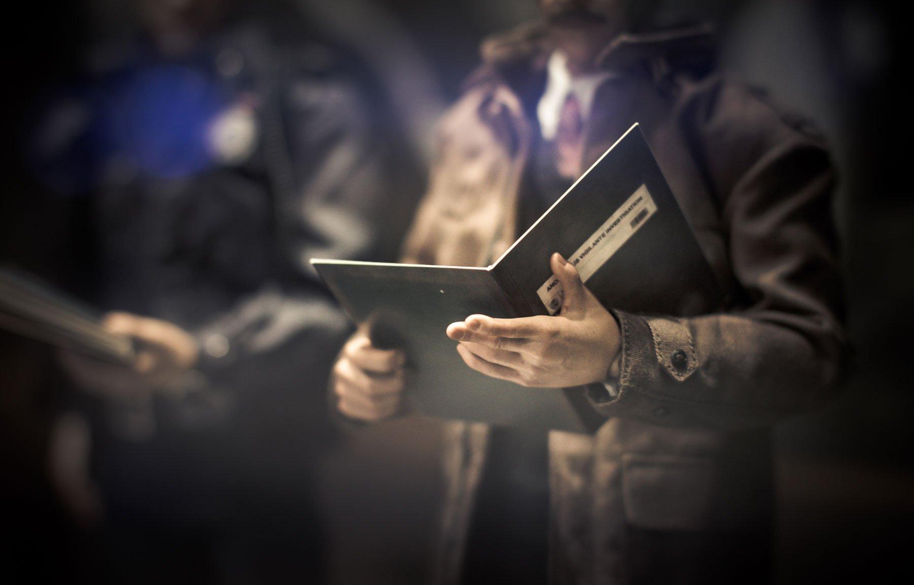 un uomo in piedi che regge con due mani una cartella con dei documenti
