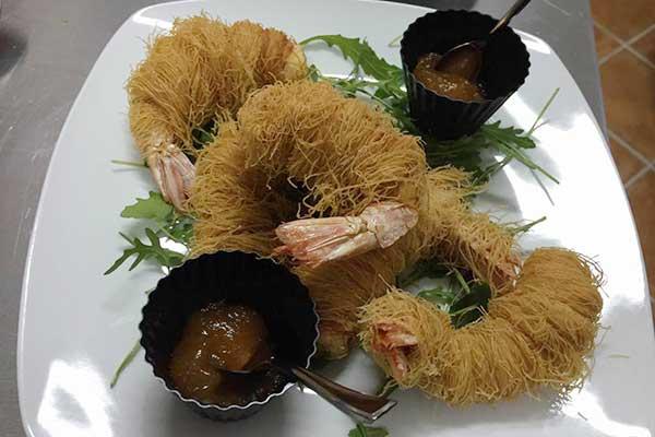 piatto a base di gamberi avvolti con dei fili e due ciotole nere con dentro della marmellata