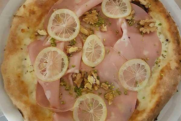 pizza bianco con prosciutto cotto,noci e fette di limone