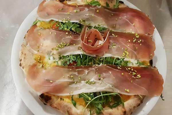 una pizza con rucola e speck
