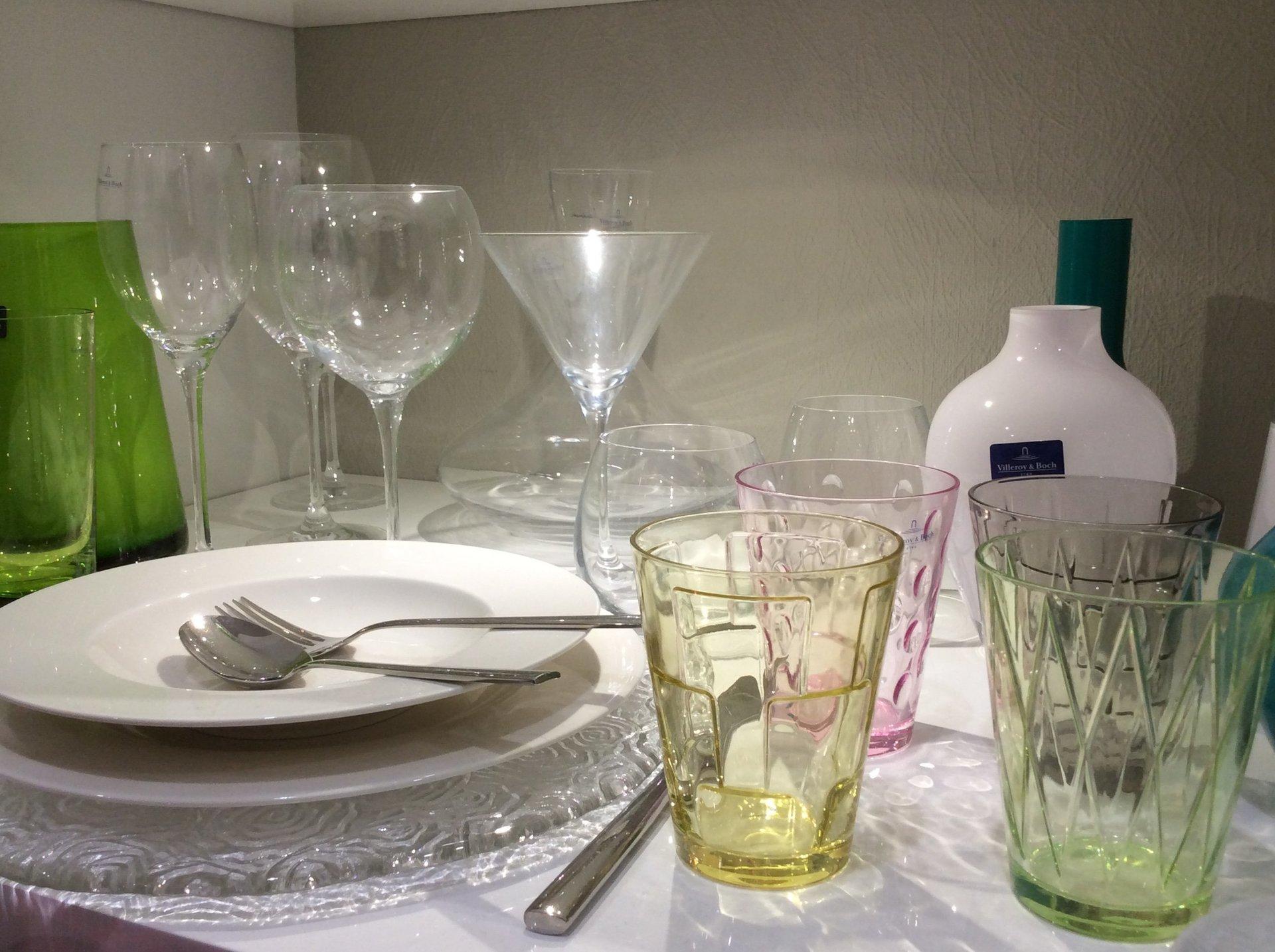 collezione di piatti in porcellana, posate in argento e bicchieri in vetro